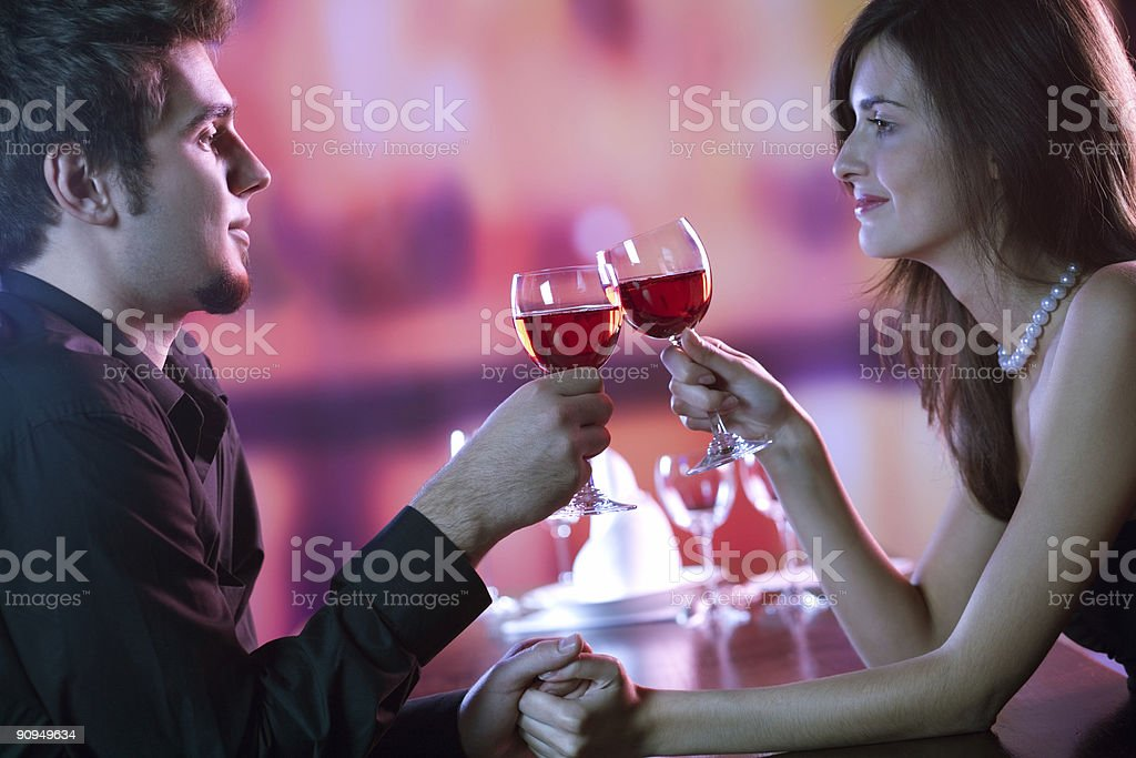 Couple sharing a glass of red wine in restaurant, celebrating royalty-free stock photo