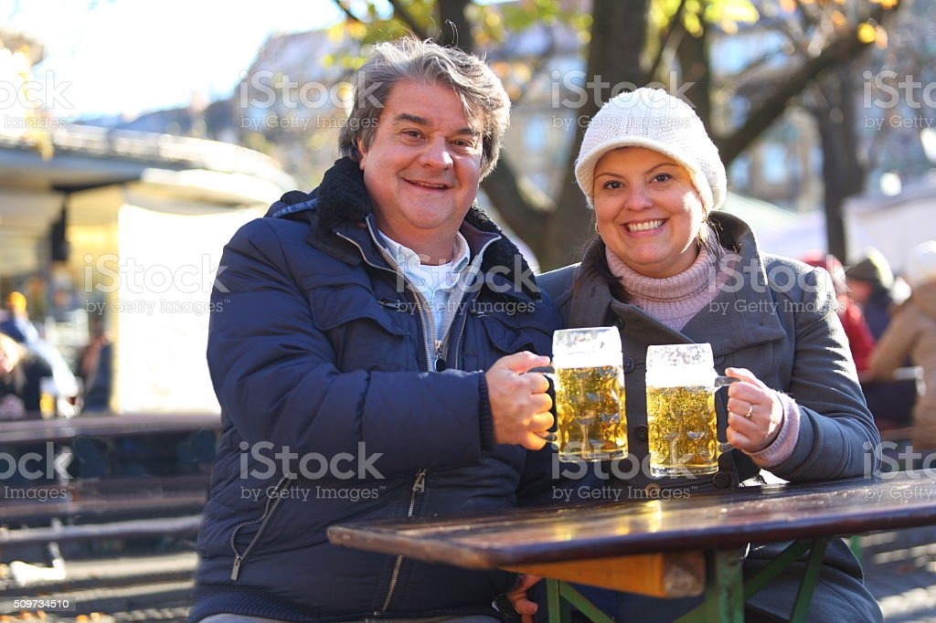 Couple Sharing Beers at Beergarden in Munich Viktualienmarkt stock photo