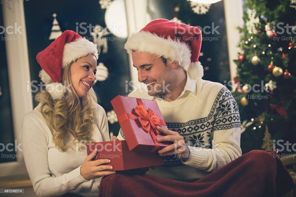 Couple sharing Christmas presents at home stock photo