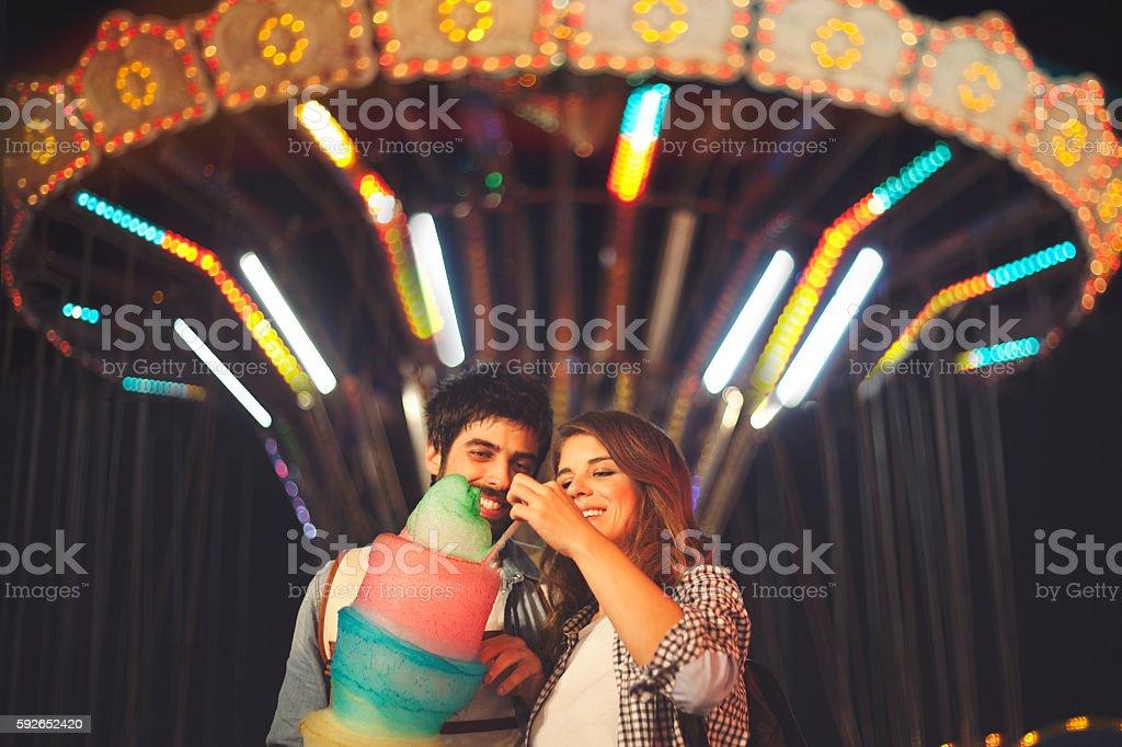 Couple sharing cotton candy at fun fair stock photo