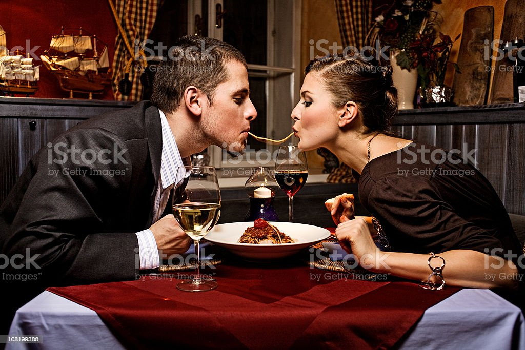 Couple Sharing Single Strand of Pasta at Dinner stock photo