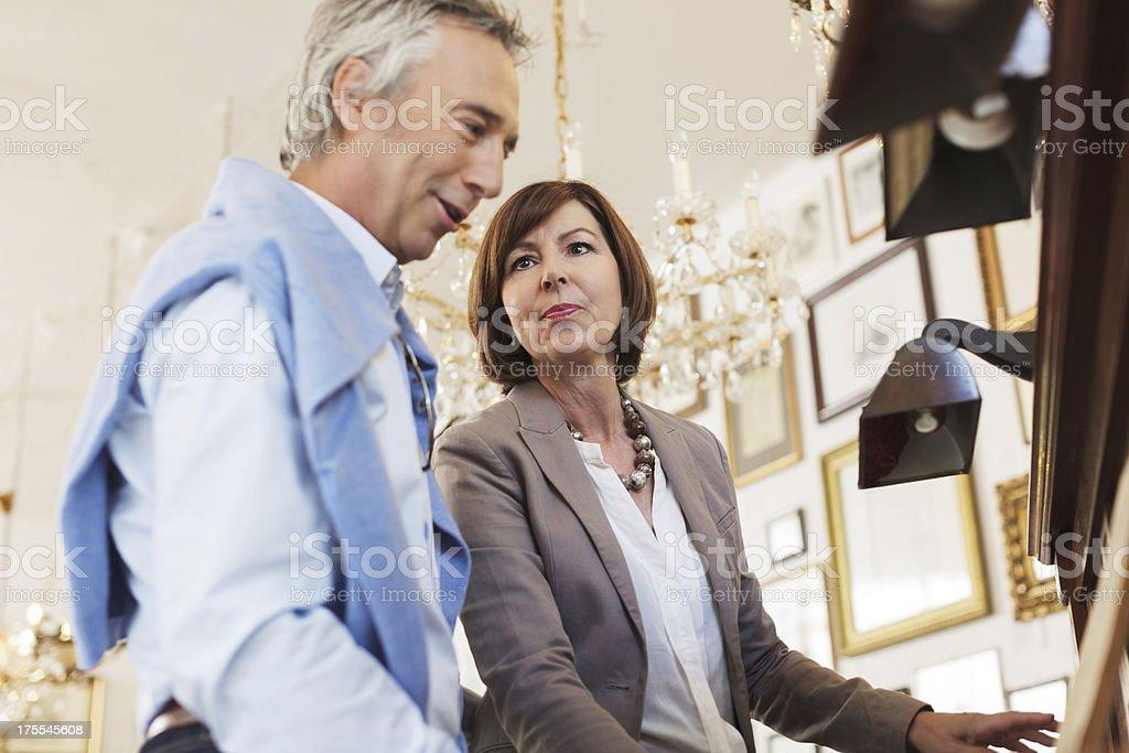 Couple shopping for antique piano stock photo