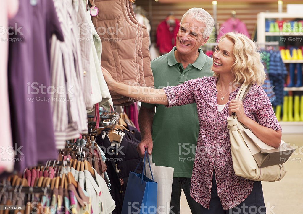 Couple shopping for clothing in store royalty-free stock photo