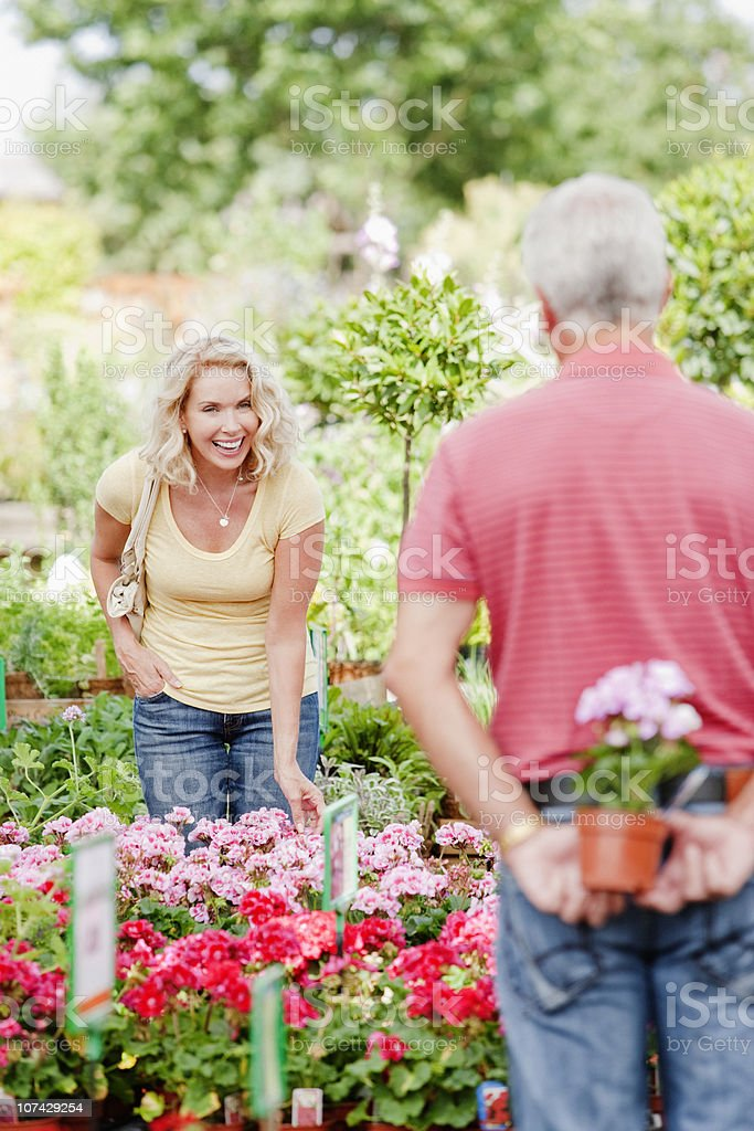 Couple shopping for flowers in nursery stock photo