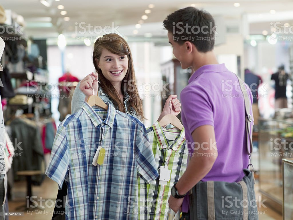 Couple shopping for shirts in store royalty-free stock photo