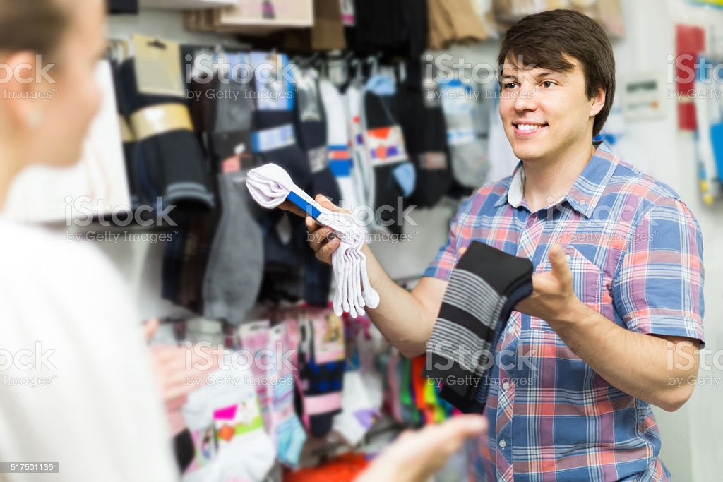 couple shops at store buying socks stock photo