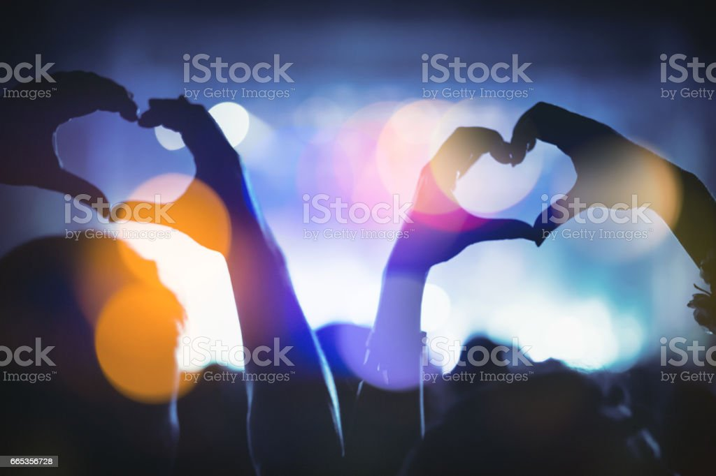 Couple showing hearts with hands at party stock photo