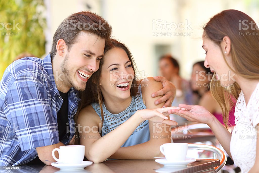 Couple showing his engagement ring to a friend stock photo