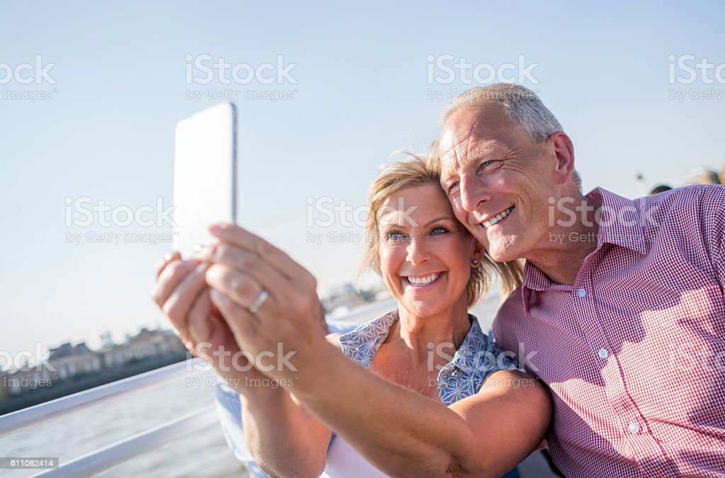 Couple sightseeing taking a selfie on a boat stock photo