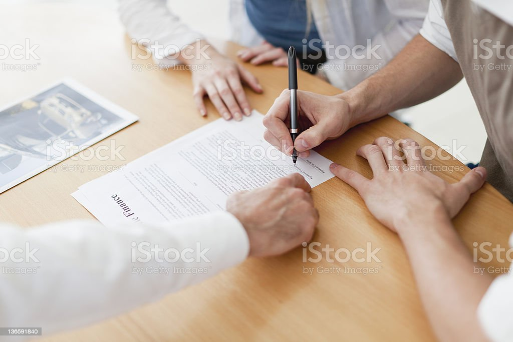 Couple signing contract with businessman royalty-free stock photo