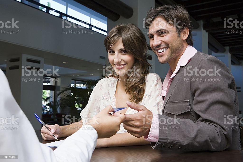 Couple signing into hotel stock photo