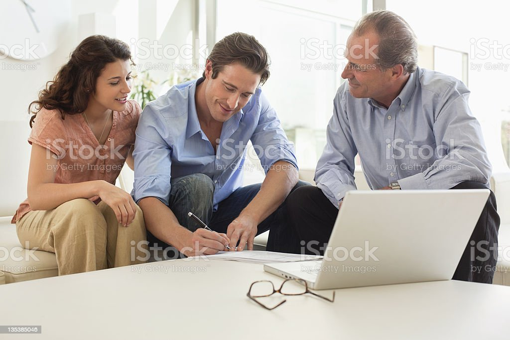 Couple signing papers with financial advisor stock photo