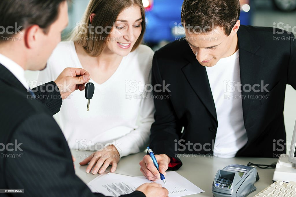 Couple signing sales contract at car dealer royalty-free stock photo