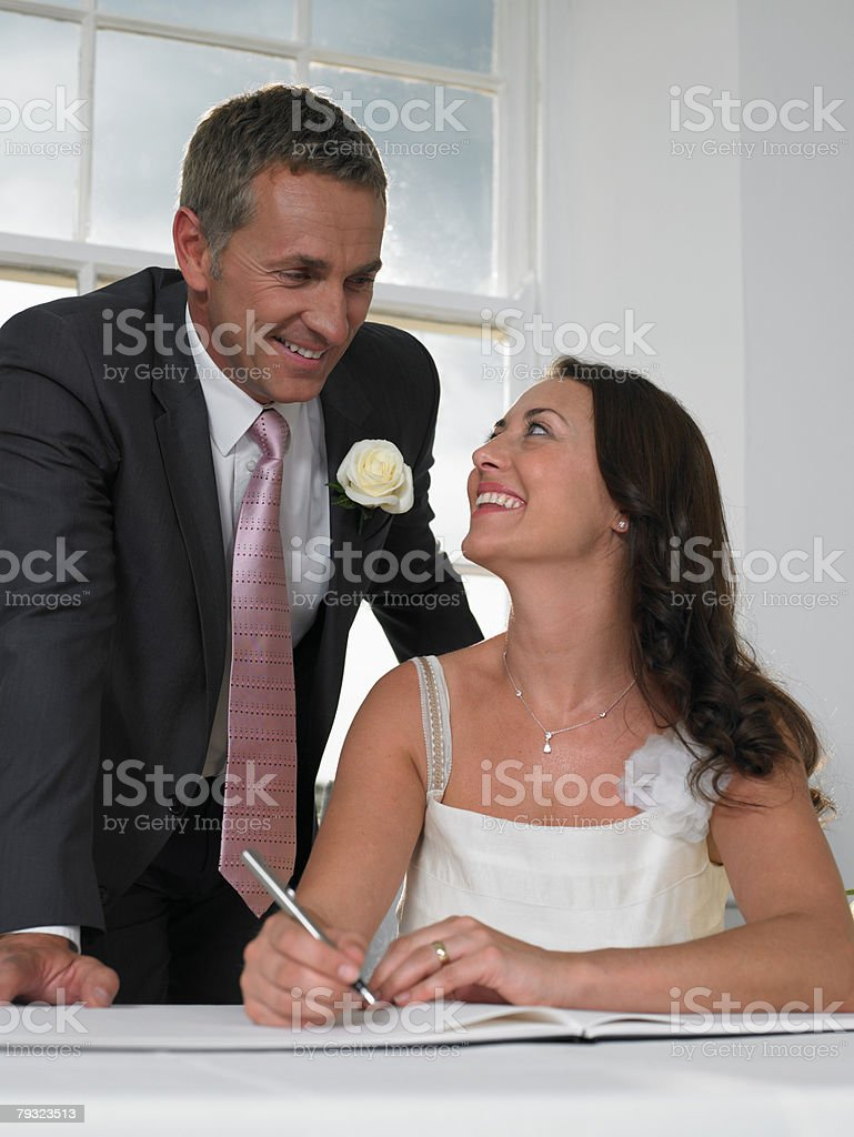 A couple signing the wedding register stock photo