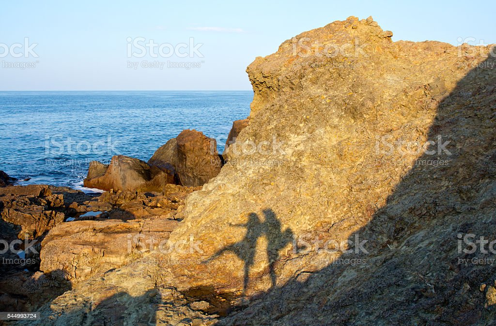 Couple silhouette reflecting on rock stock photo
