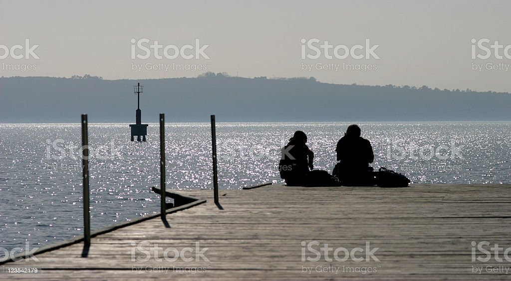 Couple silhouettes on the pier royalty-free stock photo