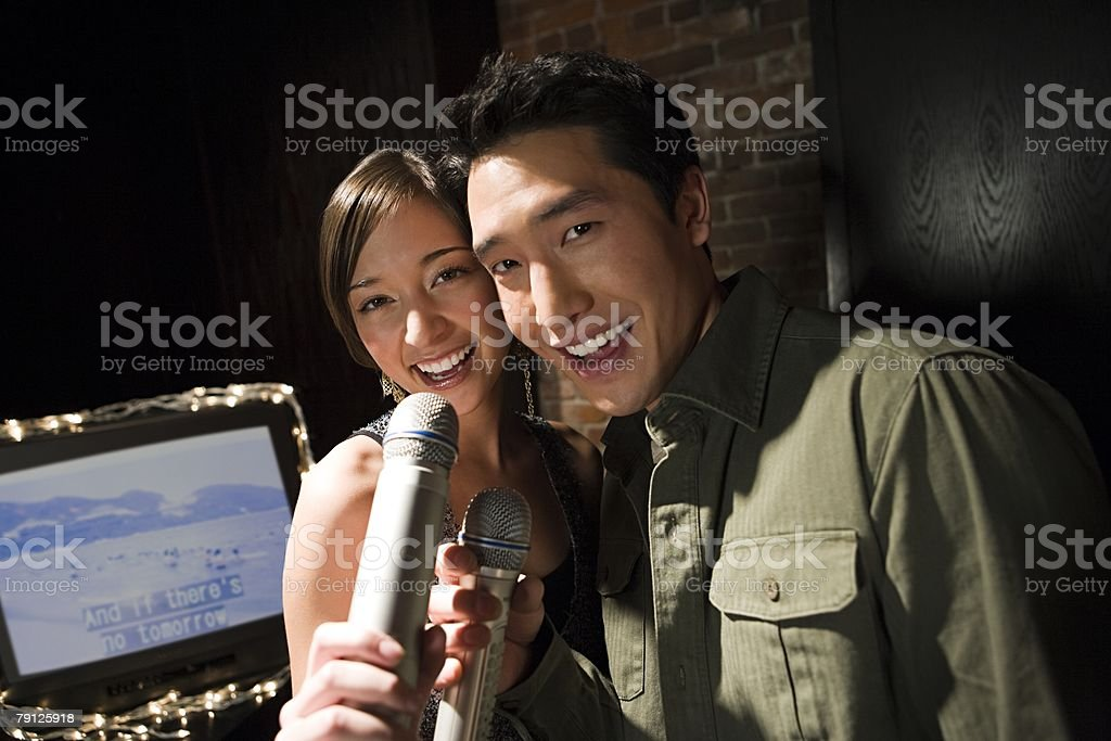 Couple singing karaoke stock photo