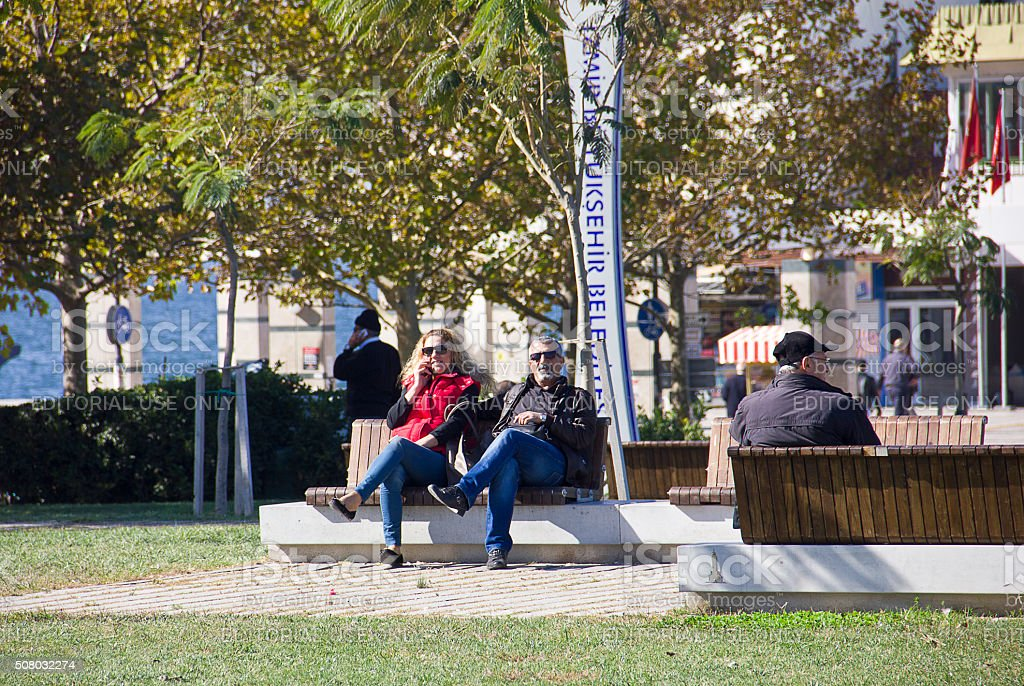 Couple sit on bench stock photo