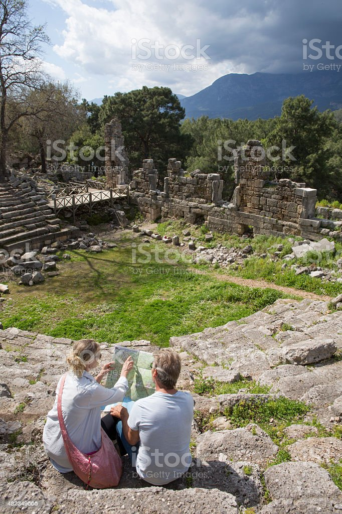 Couple sit on theatre steps of ancient Greek ruin stock photo