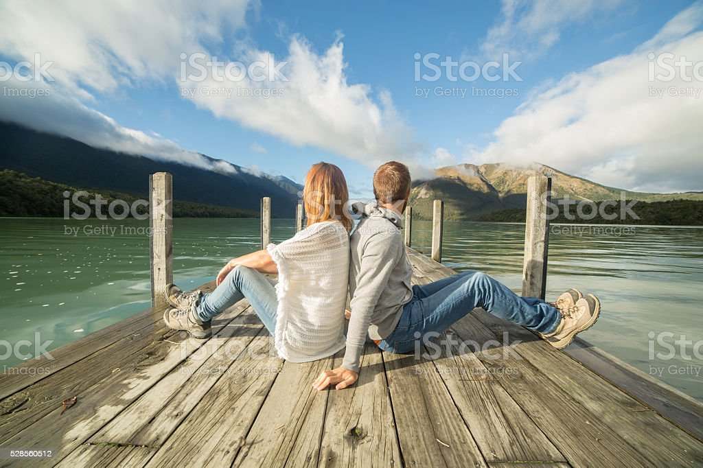 Couple sits back to back on lake pier stock photo