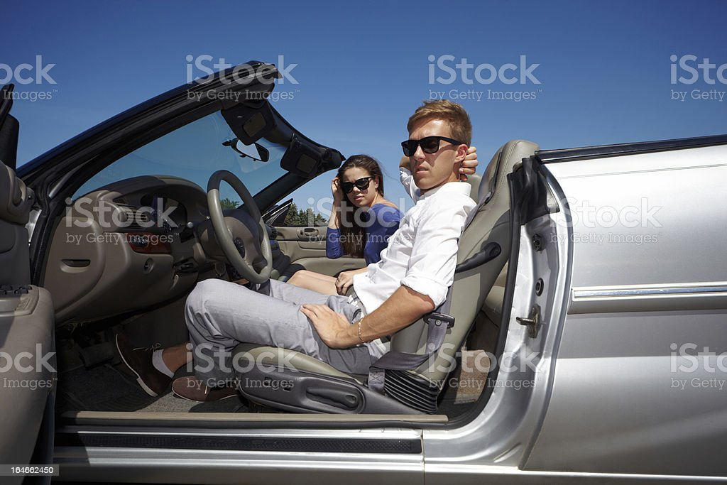 Couple sits in cabriolet and looks through open door royalty-free stock photo