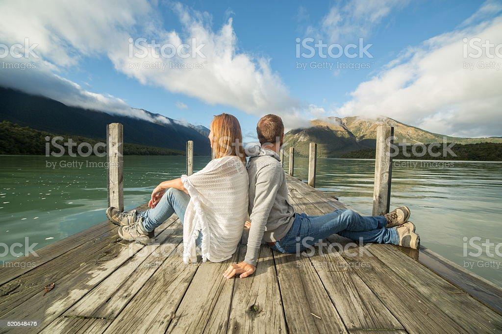 Couple sits on lake pier, enjoys landscape stock photo