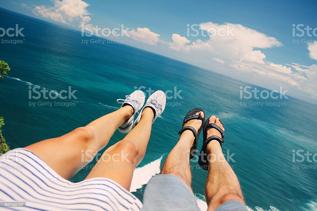 Couple sitting above the ocean stock photo