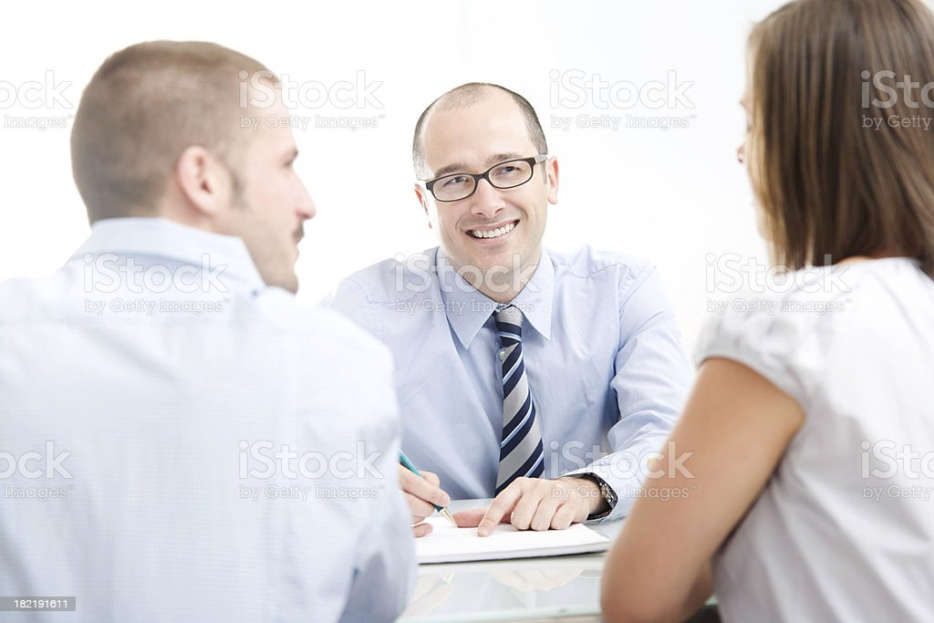 Couple sitting Across From Man At Desk Consultation royalty-free stock photo