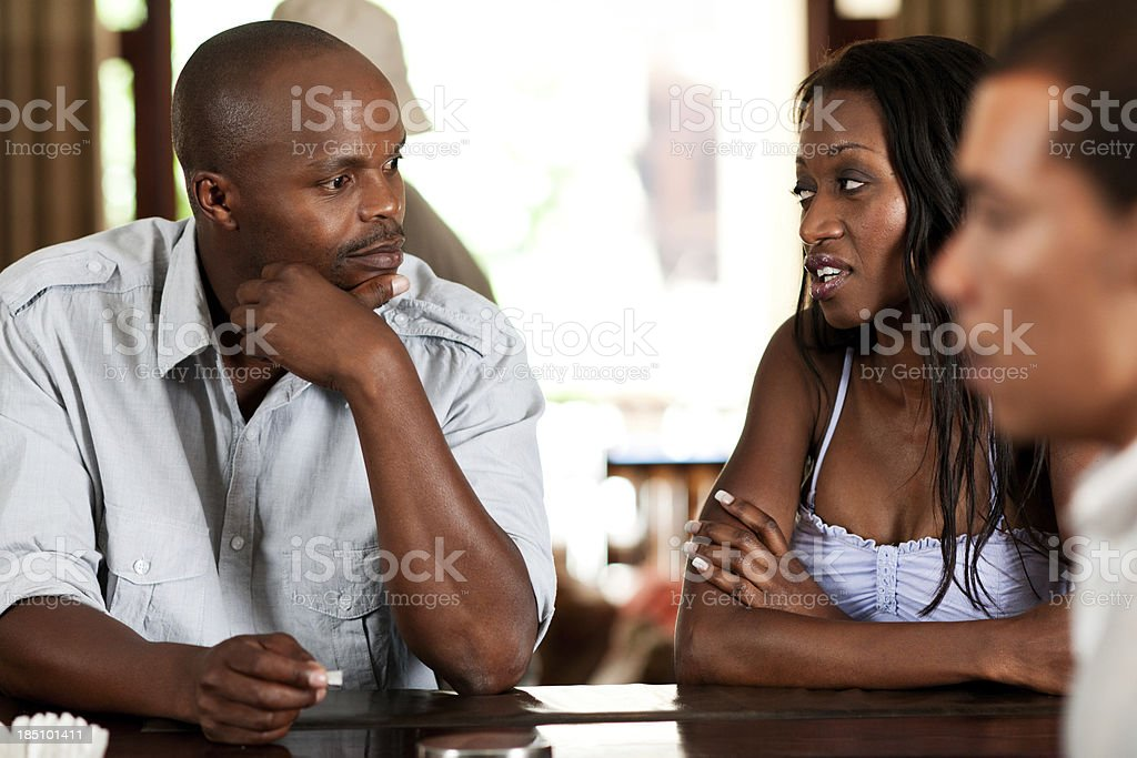 Couple sitting at bar having a deep discussion stock photo