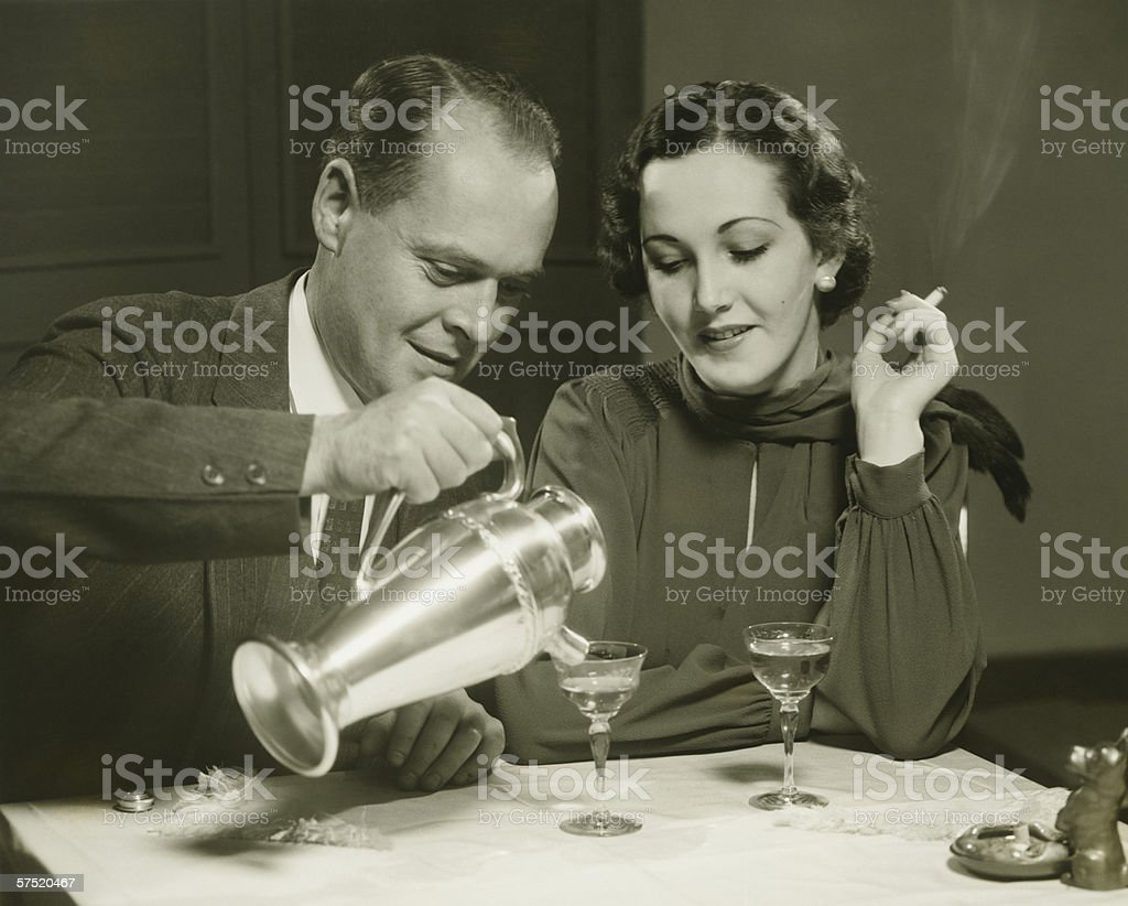 Couple sitting at table, man pouring drinks, (B&W) stock photo