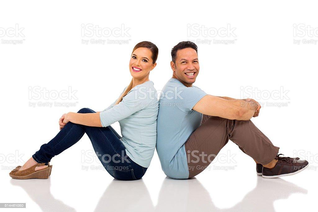 couple sitting back to back stock photo