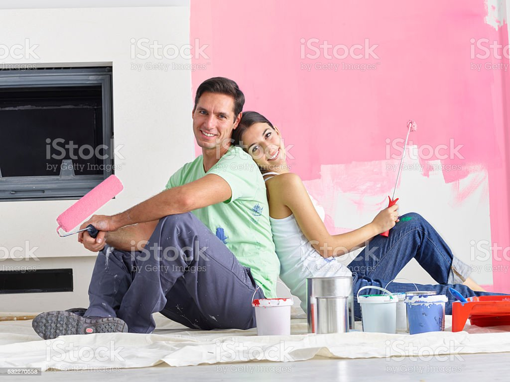 Couple sitting back to back with roller brushes in hand stock photo