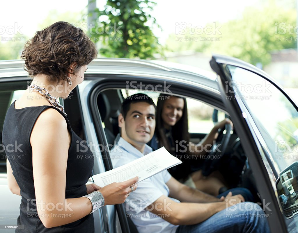 Couple sitting in a car ready to buy stock photo