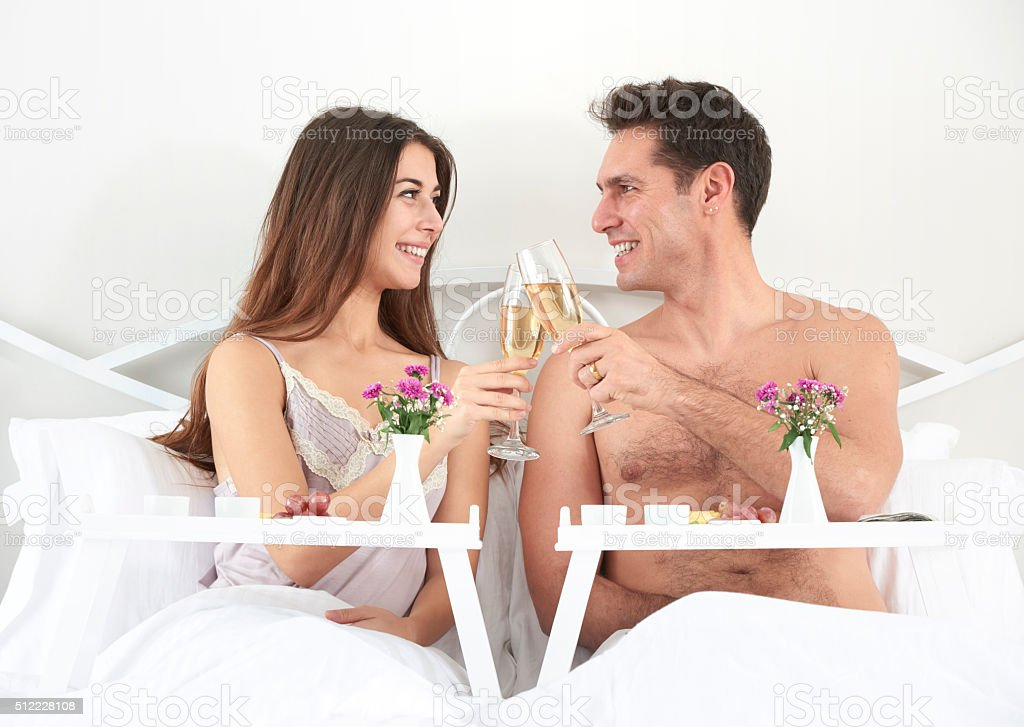 Couple sitting in bed making cheers with champagne stock photo