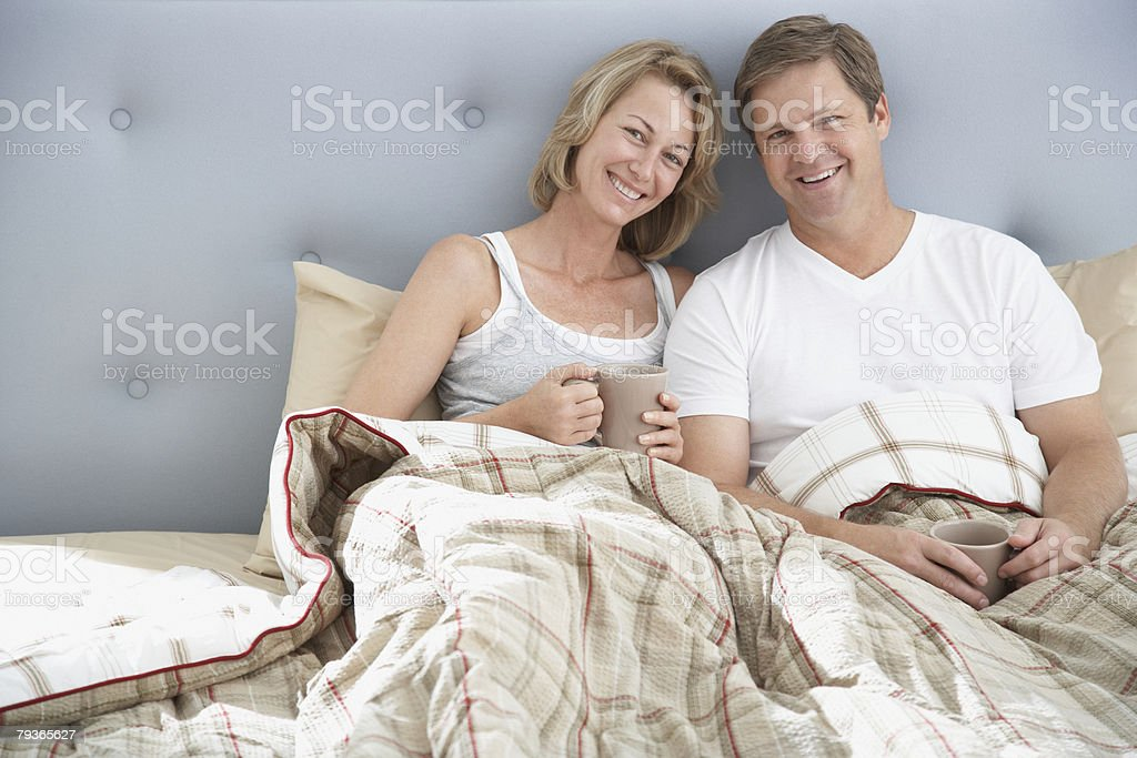Couple sitting in bed with mugs royalty-free stock photo