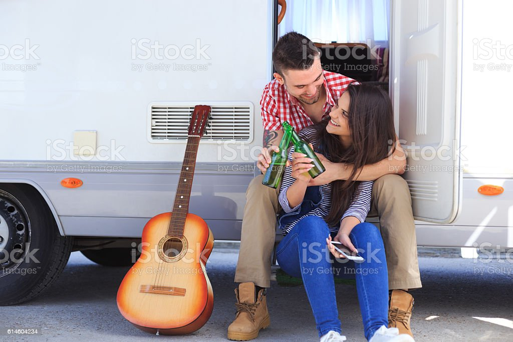 Couple sitting in front of a camper and drinking beer stock photo