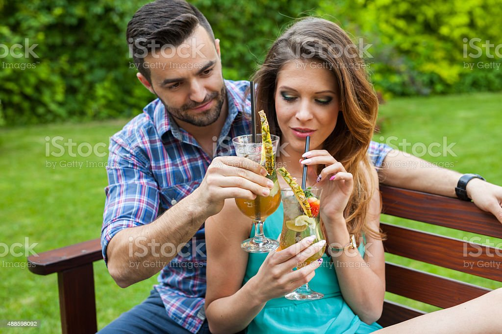 Couple sitting  in garden and having colorful drinks. stock photo