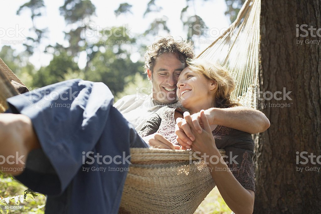 Couple sitting in hammock stock photo