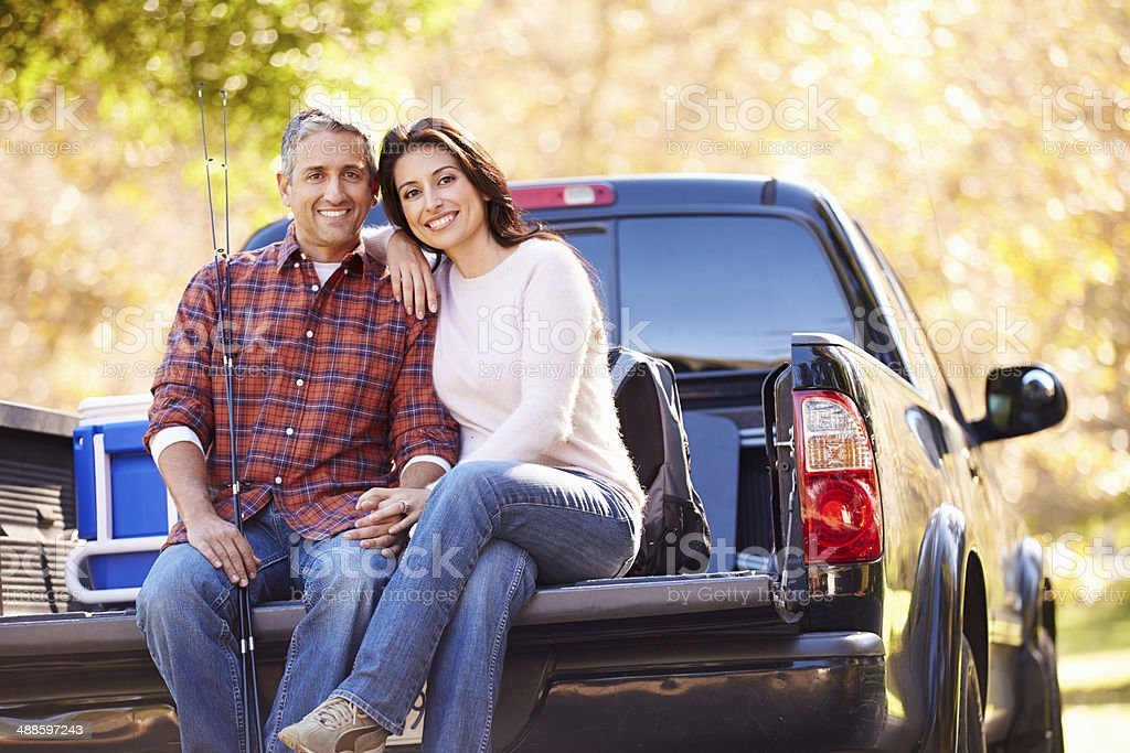 Couple Sitting In Pick Up Truck On Camping Holiday stock photo