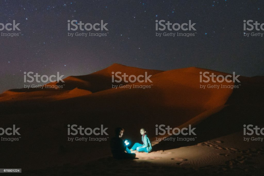Couple sitting in the desert at night stock photo