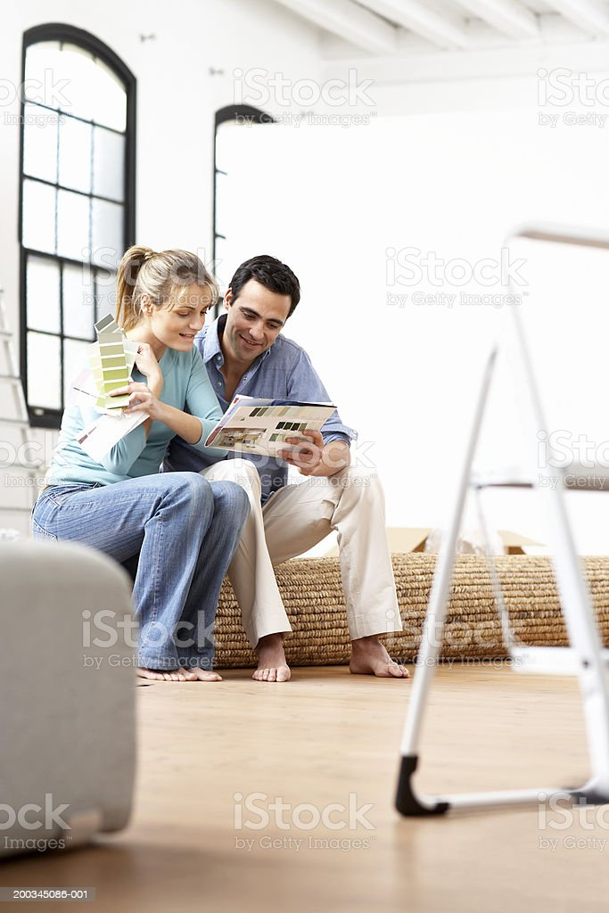 Couple sitting indoors, looking at colour charts royalty-free stock photo