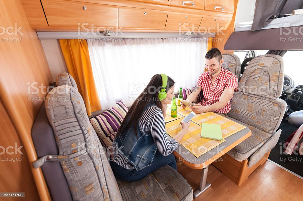 Couple sitting inside of a camper and using smart phones stock photo