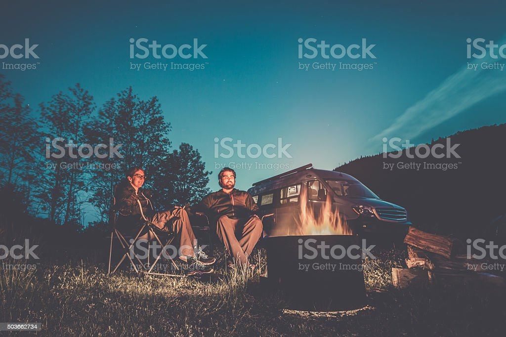Couple Sitting Next to Campfire with Camper Van stock photo
