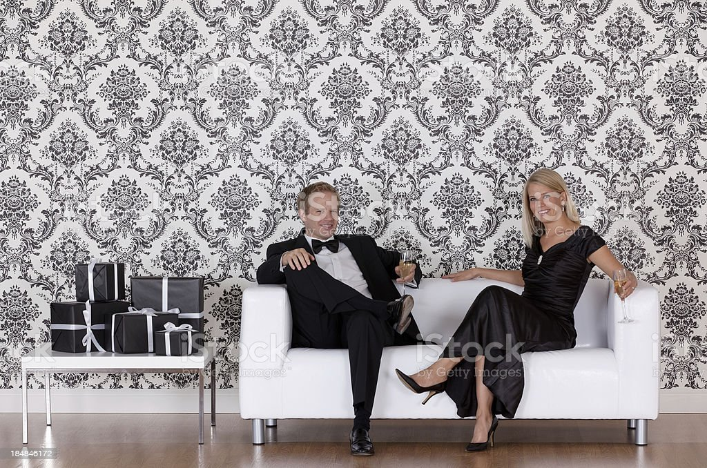 Couple sitting on a couch and smiling royalty-free stock photo