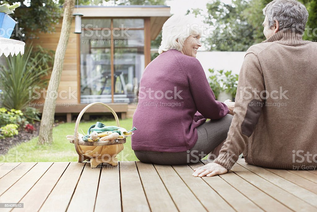 Couple sitting on backyard deck stock photo