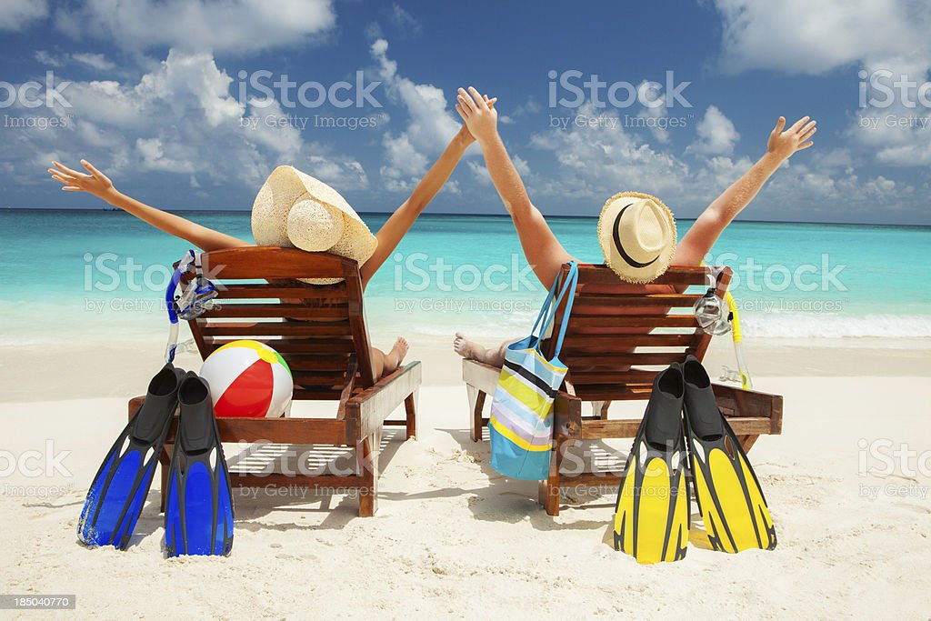 Couple sitting on beach with arms raised stock photo