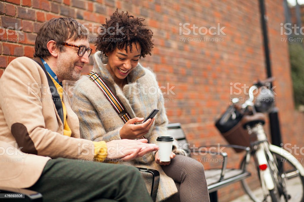 Couple sitting on bench and looking at mobile phone stock photo