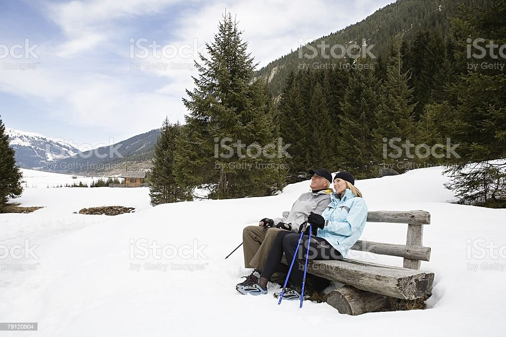Couple sitting on bench in snow royalty-free stock photo