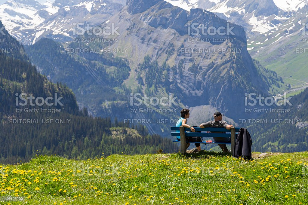 Couple sitting on bench observing amazing view of Swiss Alps stock photo