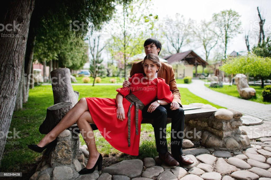 Couple sitting on bench. Stylish man at velvet jacket and girl in red dress in love together stock photo
